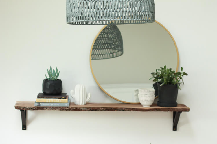 A modern minimal shelf design using plants and a round mirror. How to Decorate Shelves: Follow these simple guidelines for styling open shelving in your home | My Breezy Room